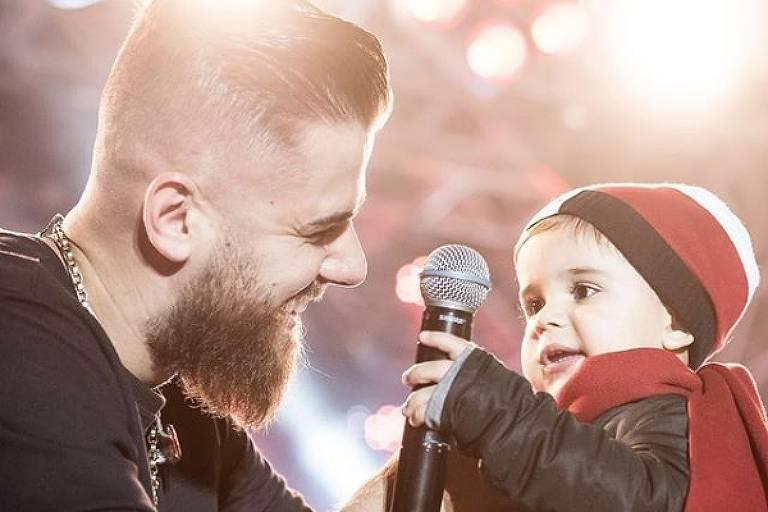 Sertanejo Zé Neto olha para seu filho José Filho. O bebê está segurando um microfone.