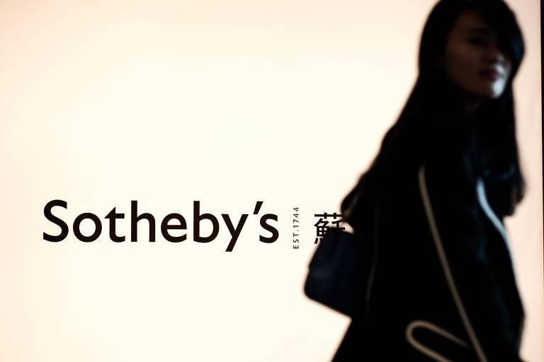 Mulher caminha em frente ao logo da casa de leilões Sotheby's