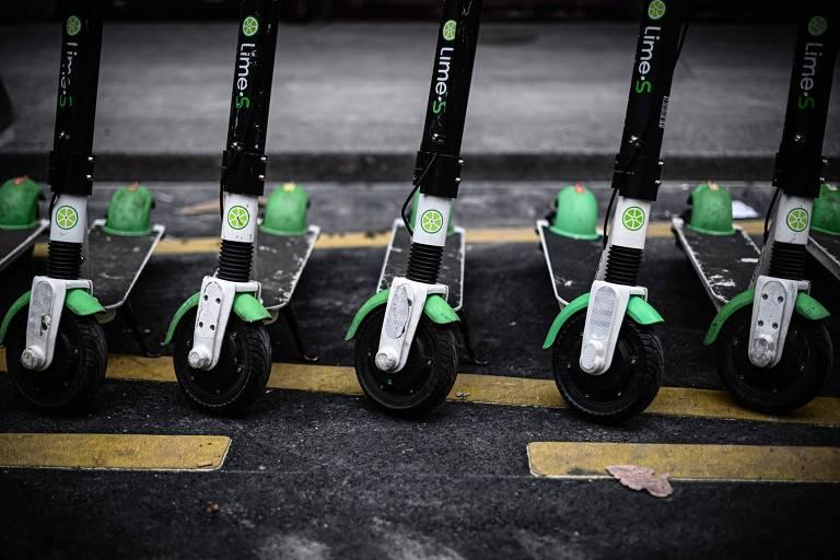 Imagem de frente mostra as rodas de cinco patinetes verde-limão e pretos enfileirados na guia de uma calçada