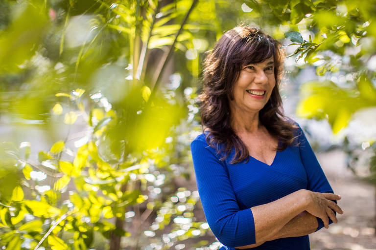 De azul, Mirian Goldenberg sorri em meio a árvores