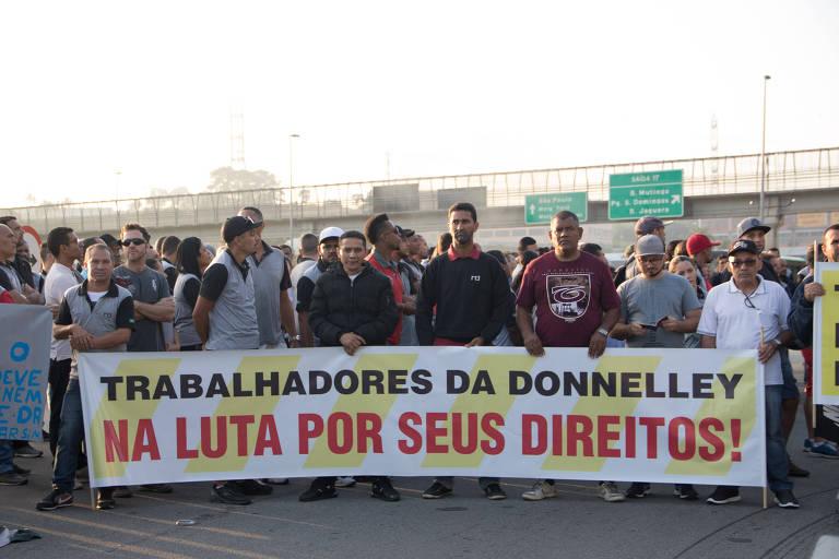 """Grupo de algumas dezenas de homens, fotografado de frente diante de um viaduto, segura faixa """"Trabalhadores da Donelley na luta por seus direitos"""""""