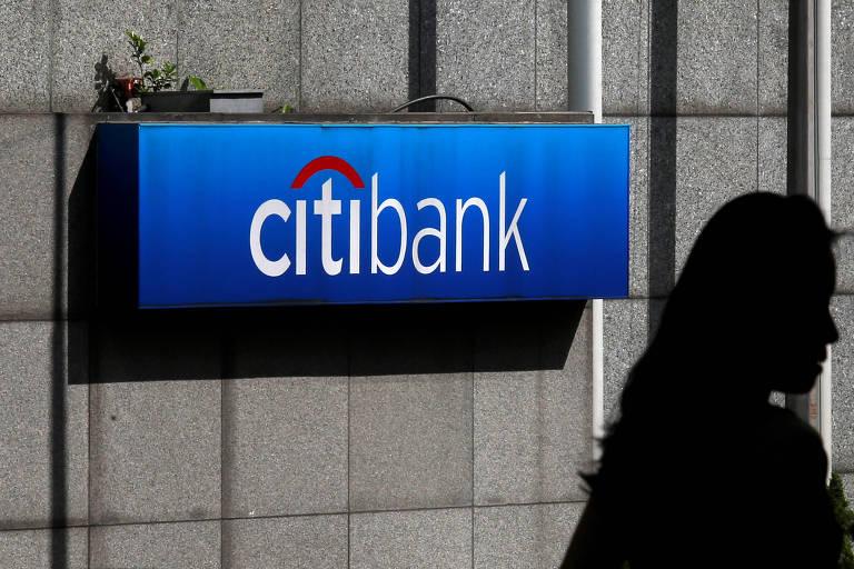 Uma mulher passa na frente do logo do Citibank