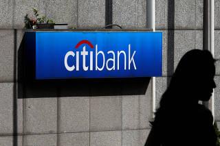 FILE PHOTO: A woman walks past a Citibank logo displayed outside the Citibank Plaza in Hong Kong
