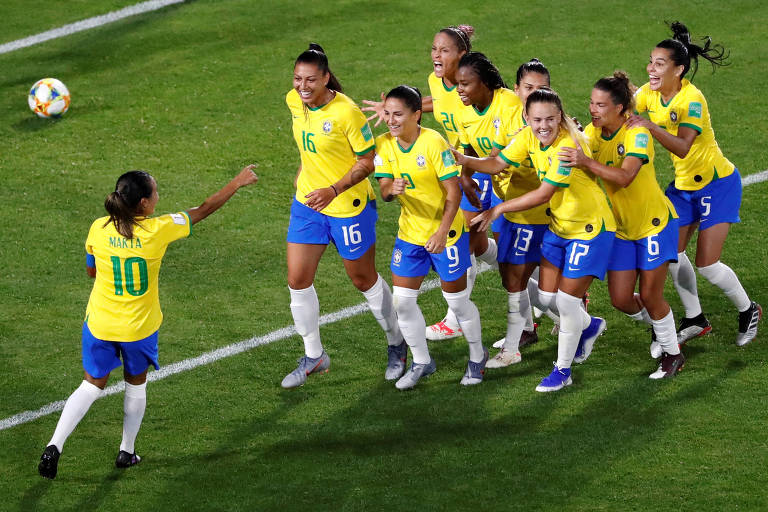 Marta aponta para grupo de jogadoras que corre na sua direção em comemoração de gol
