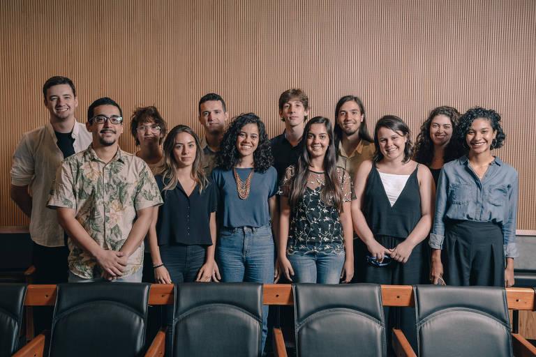 Trainees da Folha em pé no auditório posam para foto.