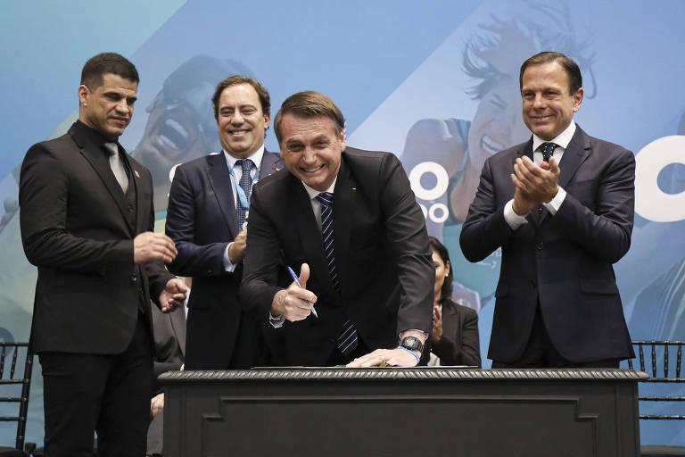 O presidente Jair Bolsonaro assina termo de compromisso em cerimônia com o presidente do Comitê Paralímpico Brasileiro, Mizael Conrado, o presidente da Caixa, Pedro Guimarães, e o governador de São Paulo, João Doria