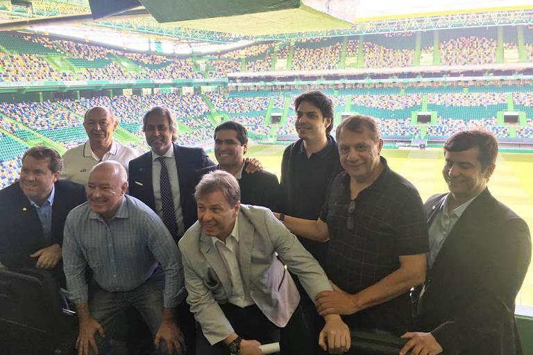 Comitiva de deputados posam para foto como um time de futebol, no estádio do Sporting, em Portugal, durante excursão autorizada pela Câmara com dinheiro público  Agachados (da esq. para a direita): Marx Beltrão (PSD-AL), Herculano Passos (MDB-SP) e Bibo Nunes (PSL-RS)  Em pé (da esq. para a direita): José Nunes (PSD-BA), um dirigente esportivo local (de gravata), Newton Cardoso Jr. (MDB-MG), Antônio José Albuquerque (PP-CE), José Airton Cirilo (PT-CE) e Luiz Antonio Teixeira Jr. (PP-RJ)