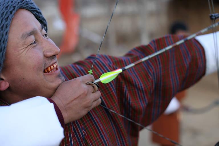 Com dentes vermelhos de 'doma', planta que é mascada e produz efeito semelhante ao da folha de coca, arqueiro se prepara durante torneio na cidade de Paro, no Butão