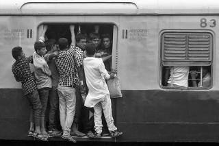 Commuters stand at an open doorway of a suburban train during the morning rush hour in Kolkata