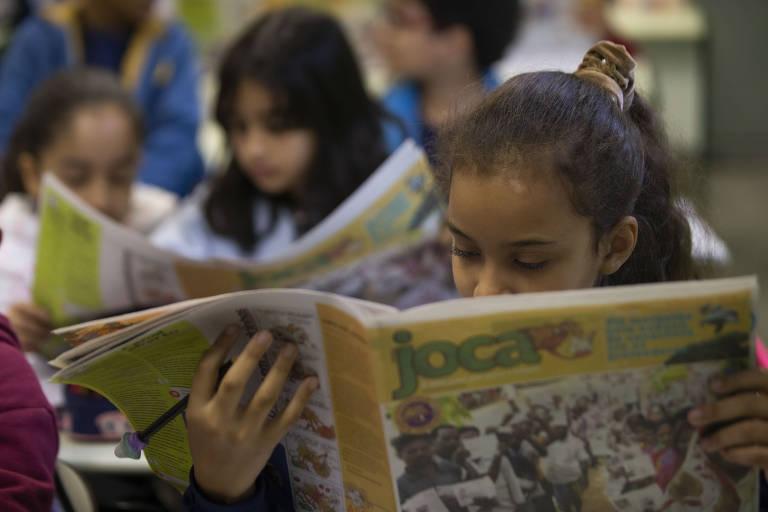 """Menina morena, com cabelos presos lê um jornal impresso com capa amarela. No alto da página lê-se """"Joca""""; ao fundo, outras crianças leem"""