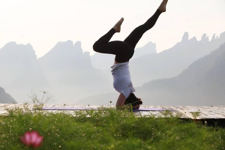 Mulher faz posição de yoga de cabeça para baixo