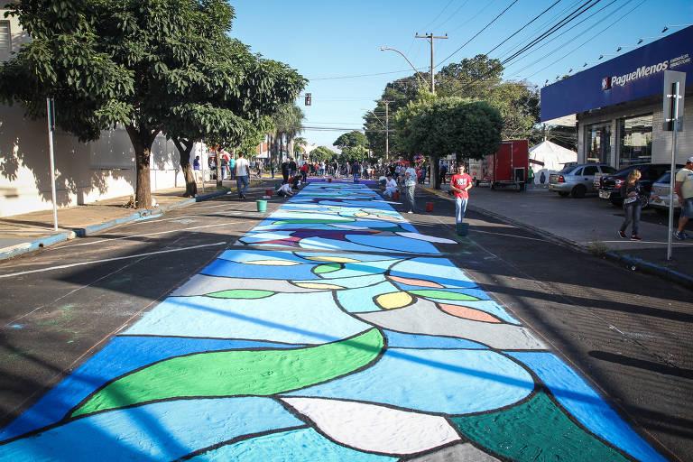 Tapete com desenhos de folhagem em azuis, verde, amarelo e cinza cobre rua de cidade