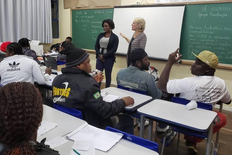 Sala de aula com repleta de alunos adultos; diante da lousa, há duas mulheres em pé viradas para eles, uma jovem negra e uma mulher loira de meia-idade