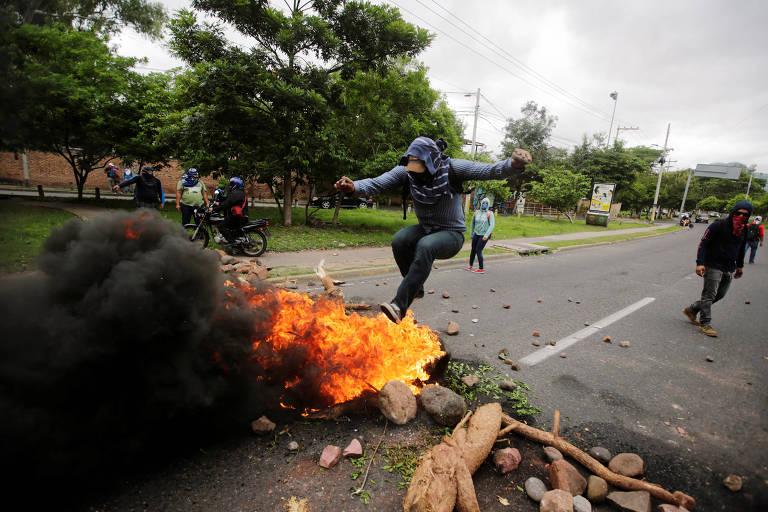 Manifestante salta sobre bloqueio montado na capital, Tegucigalpa