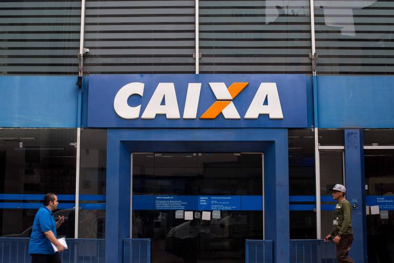 Uma agência da Caixa pode ser vista, com a cor azul predominante e várias pessoas passando em frente