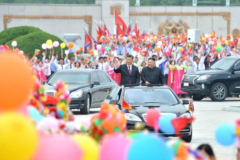 Xi Jinping e Kim Jong-Un acenam de carro de luxo para público
