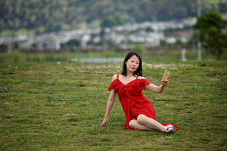 Woman takes selfies with a mobile phone near Erhai Lake in Dali