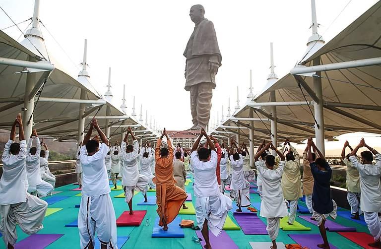 Dezenas de pessoas de costas, sobre tapetes azuis, praticam ioga