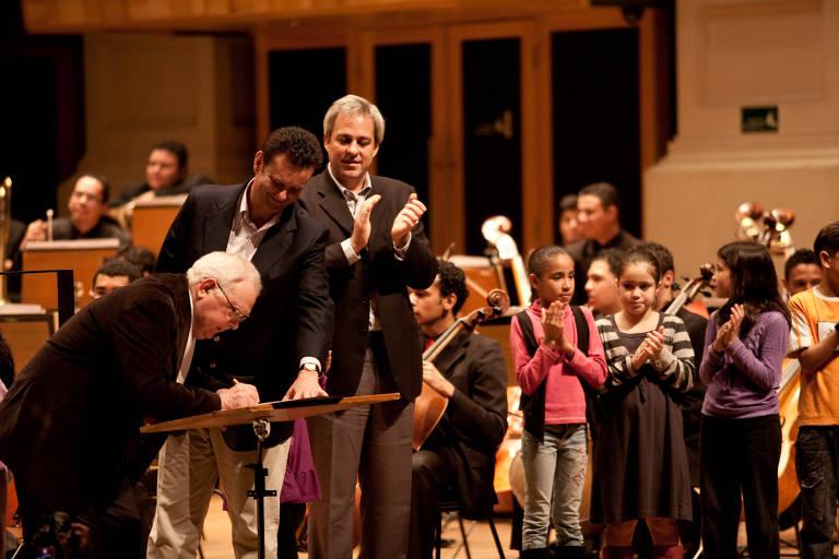 O maestro Silvio Baccarelli, em 2010, assinando parceria de seu Instituto com a Prefeitura de São Paulo, ao lado do então prefeito Gilberto Kassab