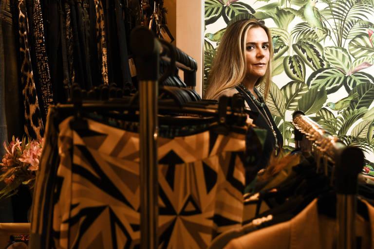 Mulher loira sentada atrás de arara de roupas