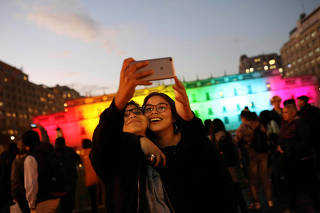 A couple take a selfie next to Chile's presidential palace La Moneda,  illuminated with the colours of the pride flag to mark the International Day Against Homophobia in Santiago