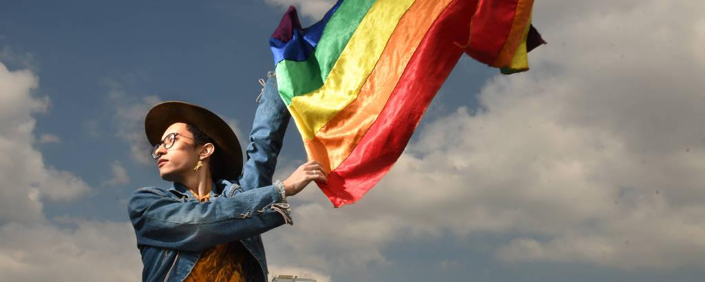 garoto no topo de um prédio segurando bandeira de arco-íris