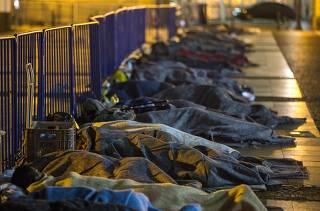 Homens e mulheres dormem diante do Pateo do Collegio, em SP