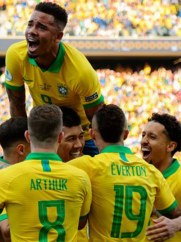 Brazil's Roberto Firmino celebrates with teammates after scoring the team's second goal against Peru during their Copa America football tournament group match at the Corinthians Arena in Sao Paulo, Brazil, on June 22, 2019. (Photo by Miguel SCHINCARIOL / AFP)