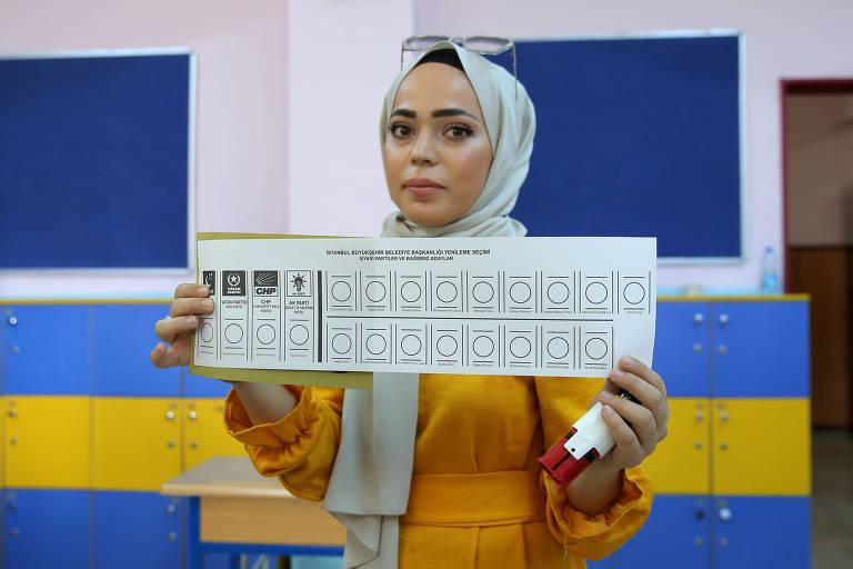 Mulher mostra cédula de votação