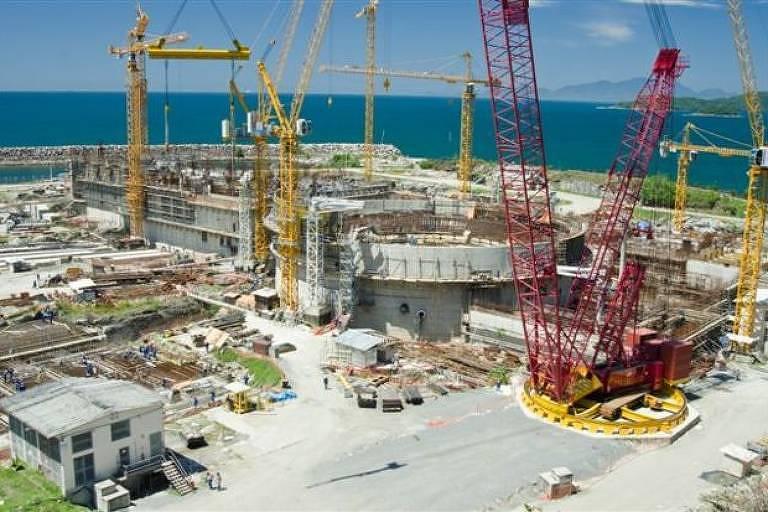 Estrutura de concreto rodeada por gruas de construção