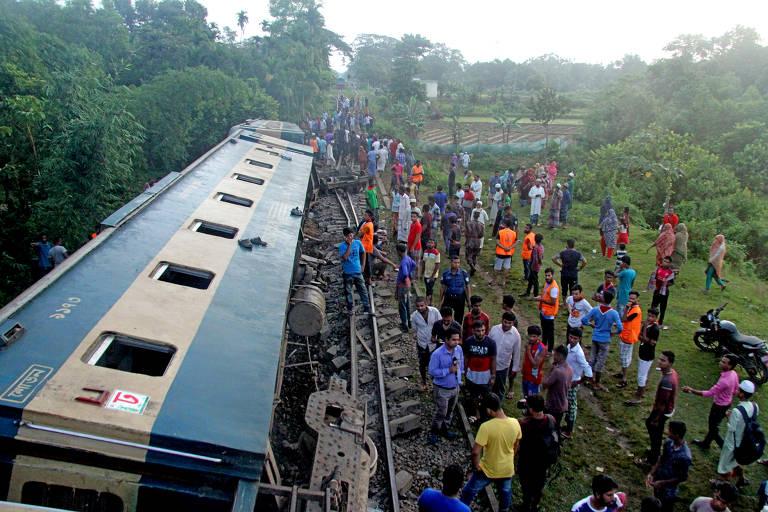 Pessoas se aglomeram perto de trilho onde há um trem tombado