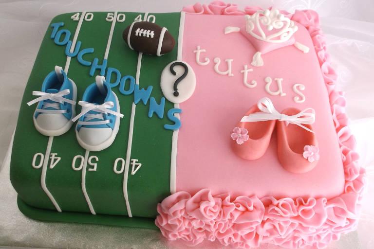 Bolo revelação da Karen's Cake Shoppe; de uma lado um campo de futebol americano, do outro, glacê rosa com sapatilhas de balé