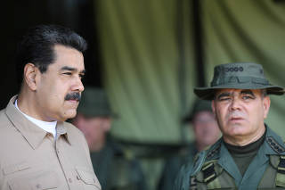 Venezuela's President Nicolas Maduro and Defence Minister Vladimir Padrino speak during a meeting with military commanders, in Caracas
