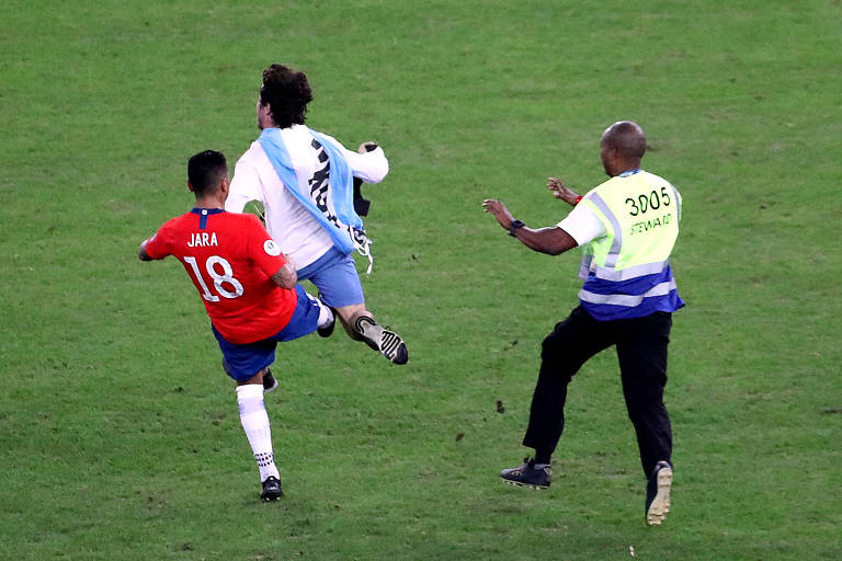O chileno Gonzalo Jara derruba o torcedor que invadiu o gramado do Maracanã