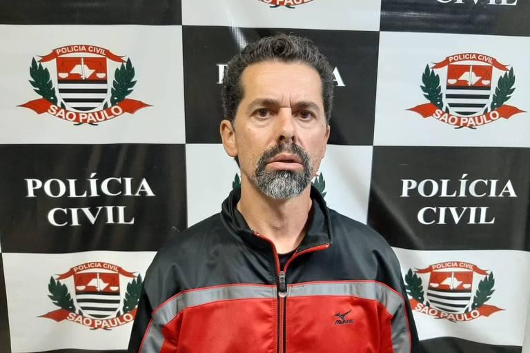 Ecio Pilli Junior, 47, em frente ao emblema da polícia civil de SP