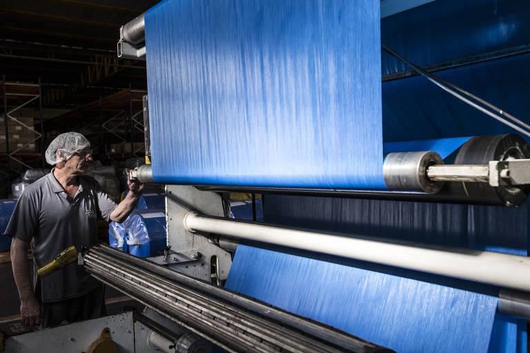 Funcionário da Boomera veste toca e uniforme cinza enquanto opera maquina que produz uma lona azul de plástico
