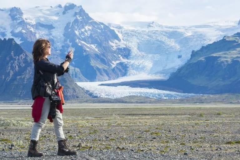 Mulher fotografa paisagem de montanhas e gelo