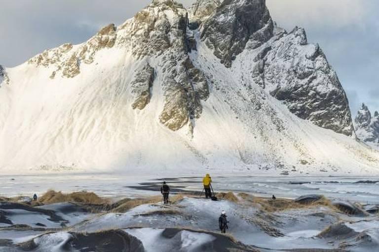 Pessoas olham para montanha com gelo