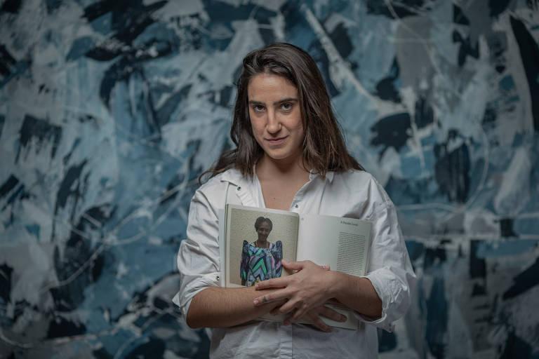 A arquiteta Mariana Montag segura um retrato de Jajja, uma mulher de Uganda que receberá a primeira casa do projeto.