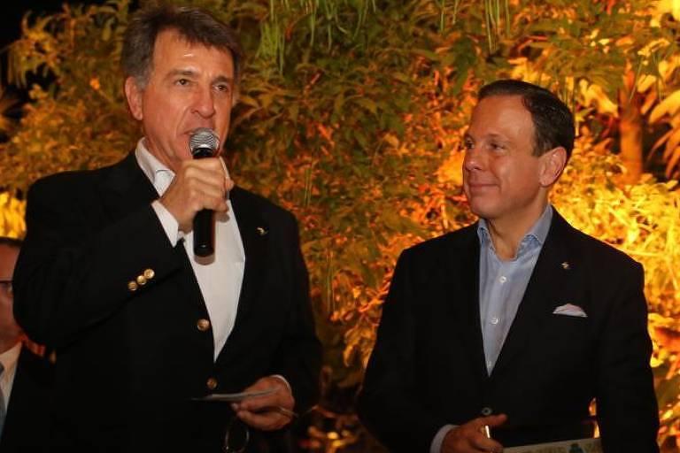 Paulo Marinho está ao lado do governador João Doria. Todos estão vestidos com a cor preta. Ao fundo vê-se plantas iluminadas por uma luz amarela.