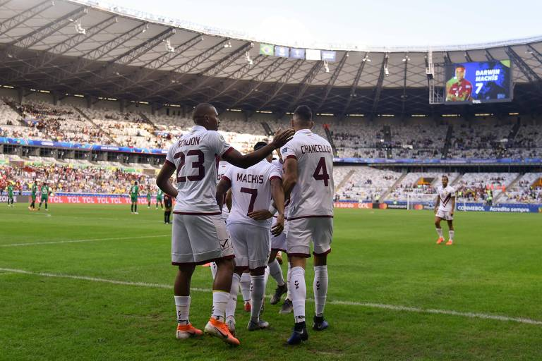 No Mineirão, jogadores da seleção venezuelana comemoram o gol marcado contra a Bolívia. Eles vestem uniformes brancos com detalhes em grená.