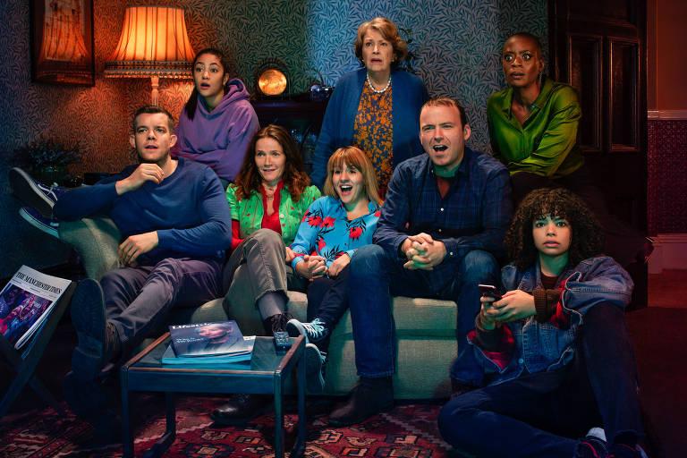 """Personagens de """"Years and Years"""" sentados em um sofá assistindo TV"""