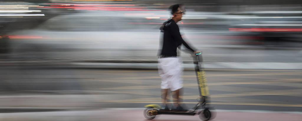 Usuário de patinete elétrico circula no cruzamento entre as avenidas Faria Lima e Juscelino Kubitschek, na zona oeste de São Paulo