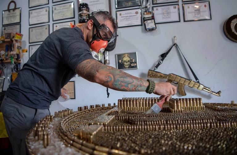 Rodrigo Camacho, 40, trabalha em obra de arte feita com balas em seu ateliê no Rio de Janeiro