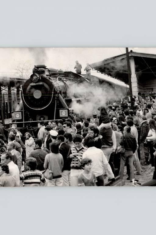 Foto em preto e branco de pessoas observando uma locomotiva maria-fumaça