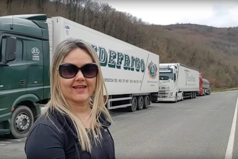 patricia posa em estrada com caminhão estaacionado ao fundo
