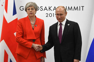 Russian President Vladimir Putin and British Prime Minister Theresa May shake hands during their meeting on the sidelines of the G-20 summit in Osaka