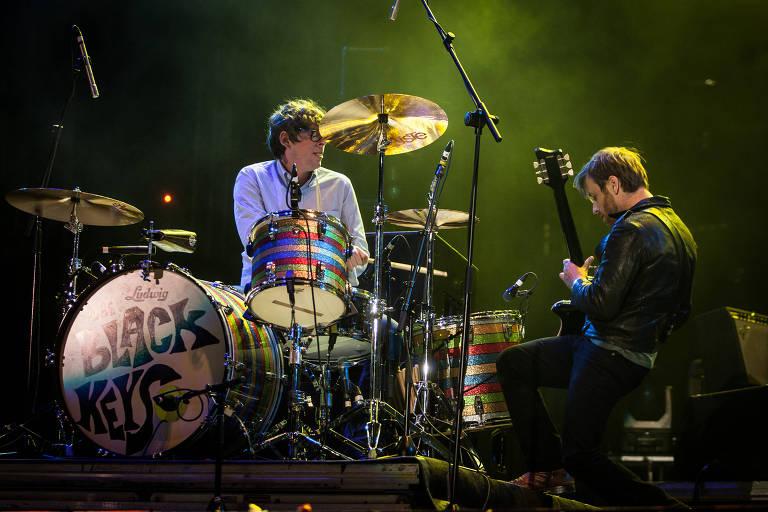 dois homens em cima do palco tocando guitarra e bateria