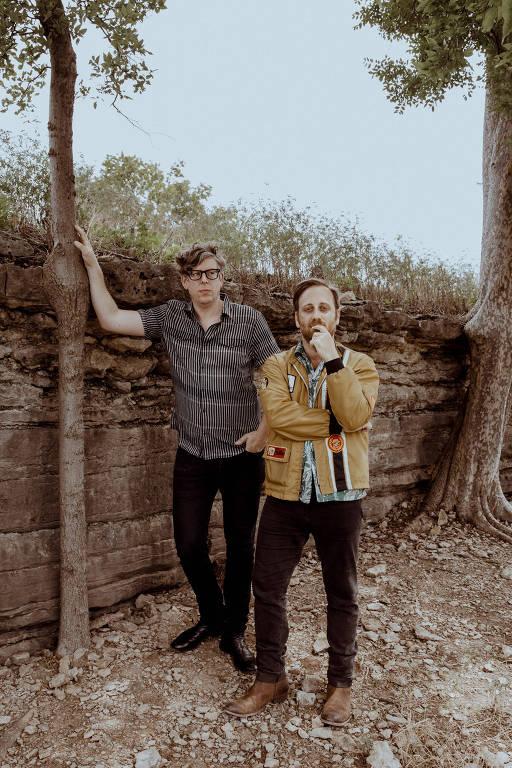dois homens de pé em um jardim