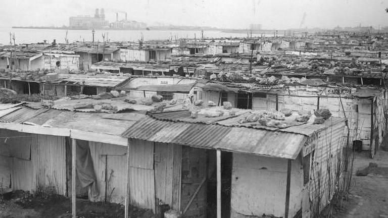 Imagem em preto e branco de barracos de favela